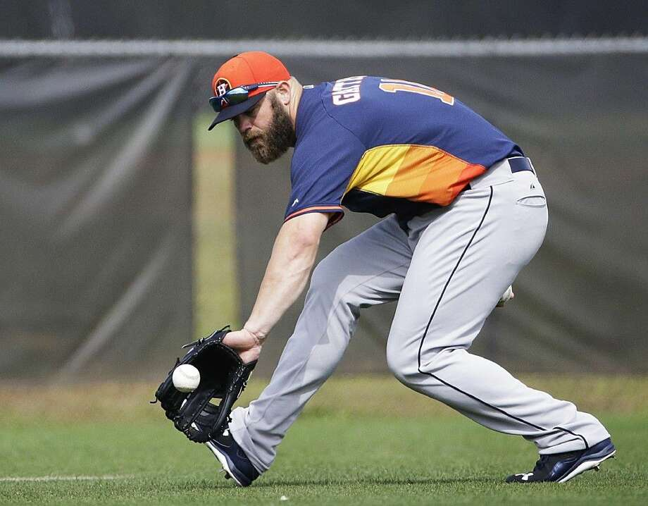 Houston Astros' Evan Gattis fields a ground ball during a spring training baseball workout, Tuesday in Kissimmee, Fla. Photo: David Goldman