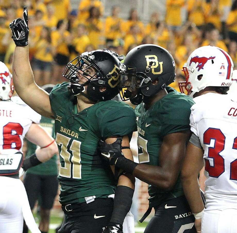 Baylor's Silas Nacita, left, is congratulated after scoring a touchdown against SMU last season.