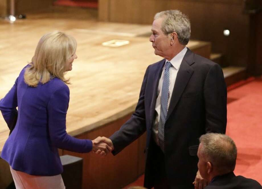 "Jill Biden, wife of Vice President Joe Biden, shakes hands with Former President George W. Bush after she spoke during a summit titled ""Empowering Our Nation's Warriors,"" held at the George W. Bush Institute at Southern Methodist University Wednesday in Dallas. Bush's policy institute is hosting the summit on helping veterans transition to civilian life."