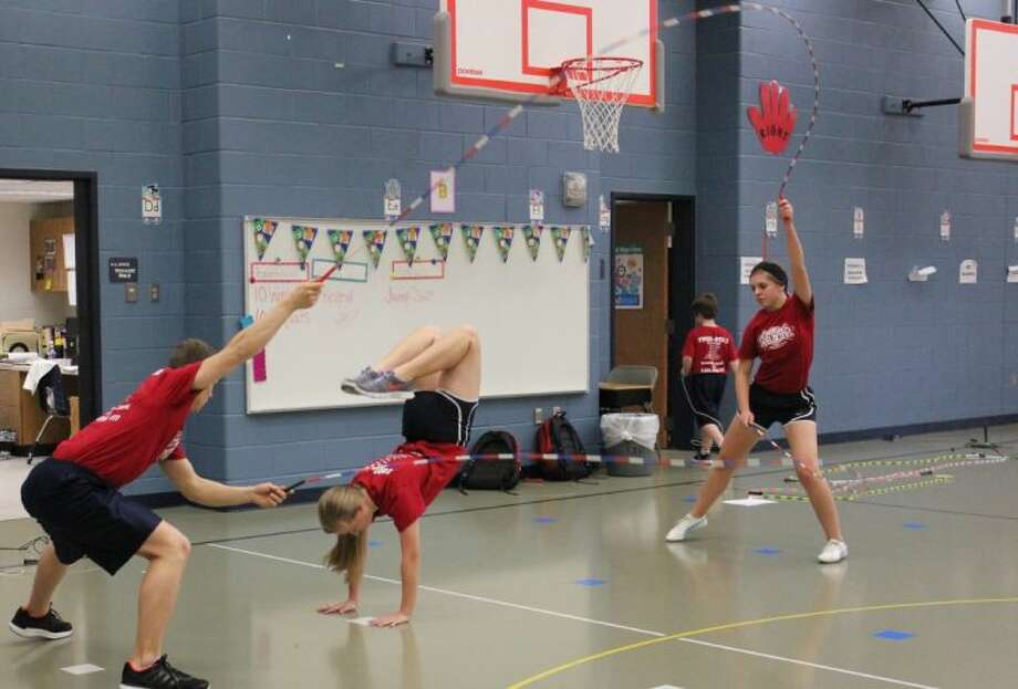 "High Velocity Jump Rope Team members Cody Caldwell and Rachel Whaley turn double dutch ropes for Sarah Hooton as she performs a ""frog,"" while encouraging students in Montgomery and Willis to be active and healthy."
