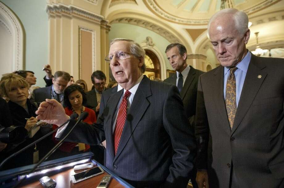 Senate Majority Leader Mitch McConnell, left, with Senate Majority Whip John Cornyn and Sen. John Thune, rear, speaks to reporters Tuesday on Capitol Hill in Washington. Photo: J. Scott Applewhite