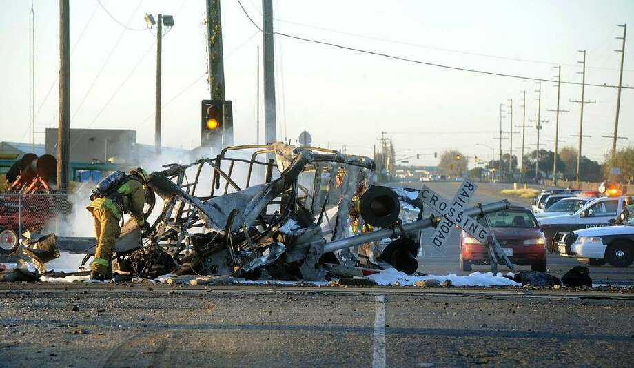 A firefighter stands near the burned wreckage of a truck that was hit by a Metrolink train that then derailed at a train crossing Tuesday in Oxnard, Calif. Three cars of the Metrolink train tumbled onto their sides, injuring dozens of people in the town 65 miles northwest of Los Angeles. Photo: Juan Carlo