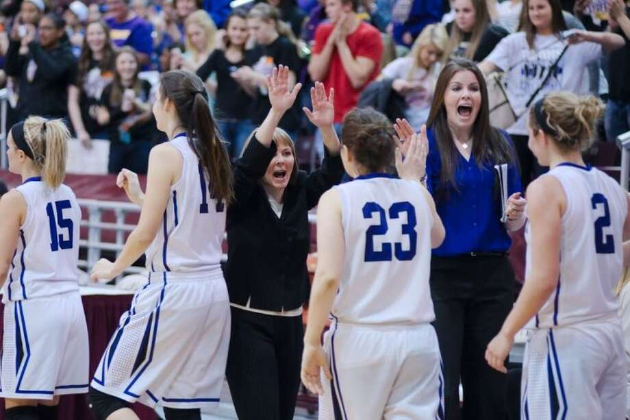 Montgomery basketball coaches Stacey Blalock, second from right, and Kip Anderson offer high fives to players after the Lady Bears defeated Friendswood in the Region III-4A basketball tournament.