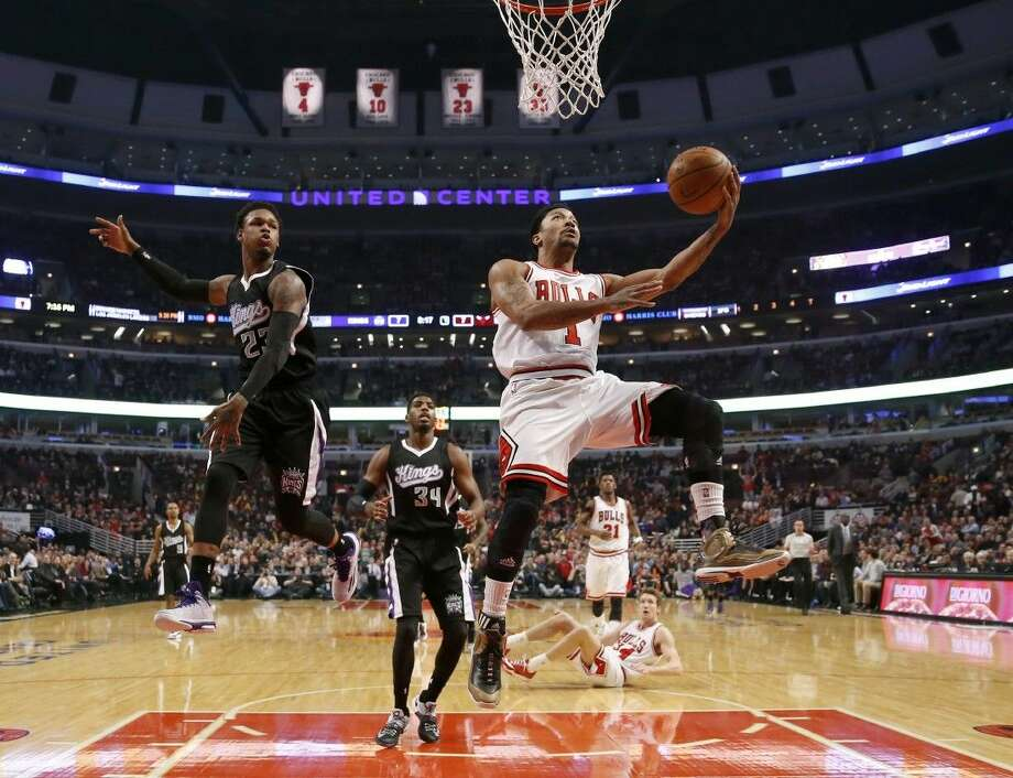 Chicago Bulls guard Derrick Rose drives past Sacramento Kings guard Ben McLemore as Jason Thompson watches during an NBA basketball game in Chicago. Photo: Charles Rex Arbogast