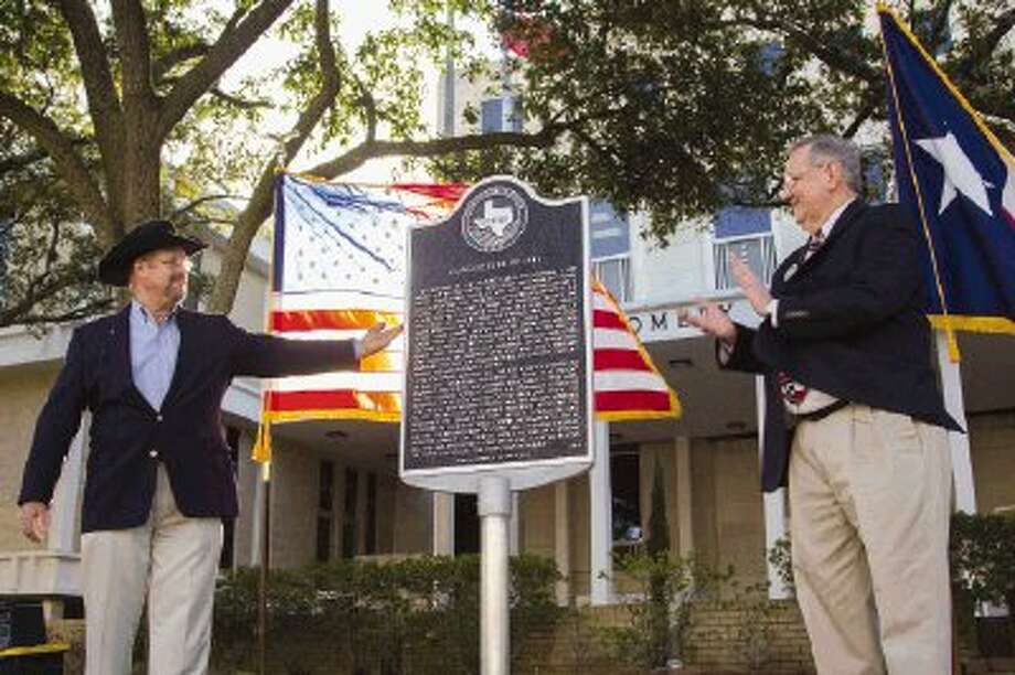Ron Saikowski helps Larry Foerster unveil a Texas historical marker during a dedication ceremony of the Conroe Fire of 1911 as an official Texas Historical Marker Friday outside of the Montgomery County Courthouse in Conroe. On Feb. 21, 1911, a fire destroyed 65 buildings in downtown Conroe. / The Conroe Courier/ The Woodland