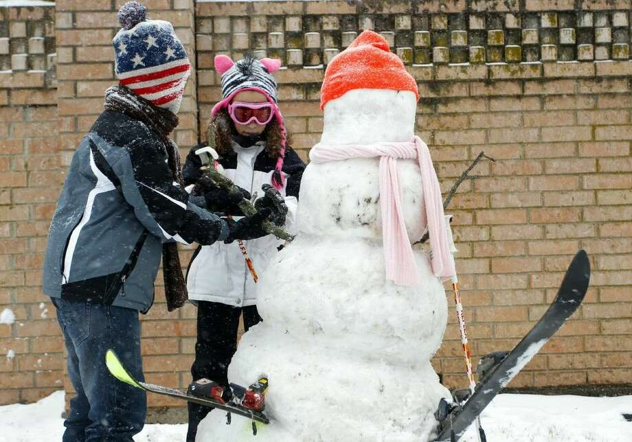 Siblings David and Celine Terry on Friday decorate the snowman they built along Glade Road in Colleyville. Photo: Richard W. Rodriguez