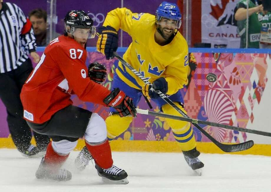 Canada forward Sidney Crosby, left, controls the puck against Sweden defenseman Johnny Oduya during the second period of the men's gold medal game. Canada won 3-0. Photo: Matt Slocum