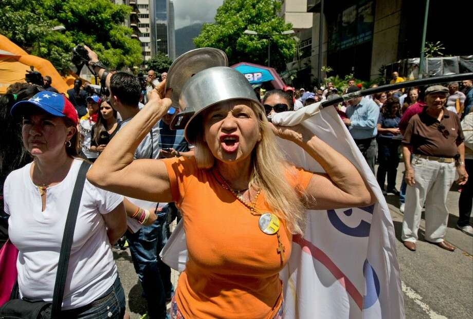 An opposition member wearing a pot on her head shouts slogans against Venezuela's President Nicolas Maduro during a protest in Caracas, Venezuela Saturday. Photo: Fernando Llano