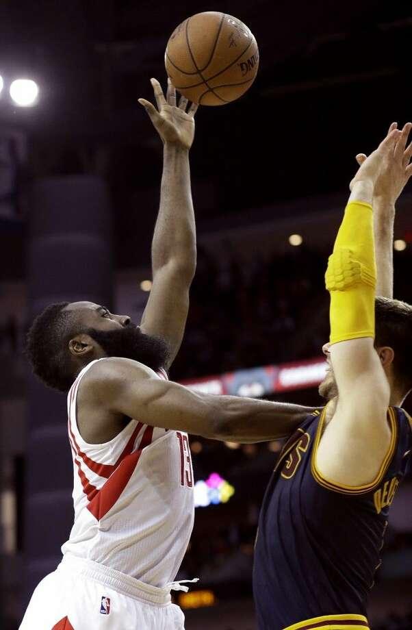 Rockets guard James Harden, left, pushes against the Cleveland Cavaliers' Matthew Dellavedova. The Rockets won 105-103. Photo: Pat Sullivan