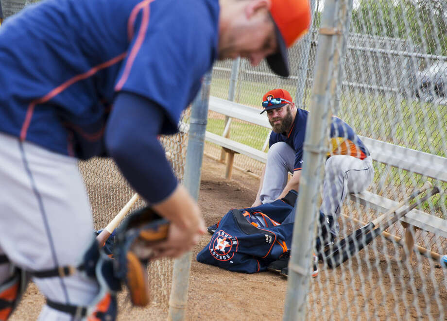 Houston Astros' Evan Gattis, right, changes his shoes as teammate Jason Castro suits up for a catching drill during a spring training baseball workout, Tuesday, Feb. 24, 2015, in Kissimmee, Fla. (AP Photo/David Goldman)