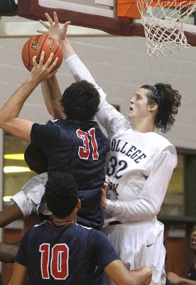 College Park's Brett Reed goes up to block a shot by Atascocita center Zach Haney during a Region II-5A regional quarterfinal playoff game at the M.O. Campbell Educational Center Tuesday. Atascocita defeated College Park 78-53. To view or purchase this photo and others like it, visit HCNpics.com.
