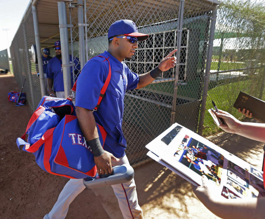Texas Rangers' Elvis Andrus waves to autographs seekers as he walks between drills during spring training baseball practice Friday, Feb. 27, 2015, in Surprise, Ariz. (AP Photo/Charlie Riedel) Photo: Charlie Riedel