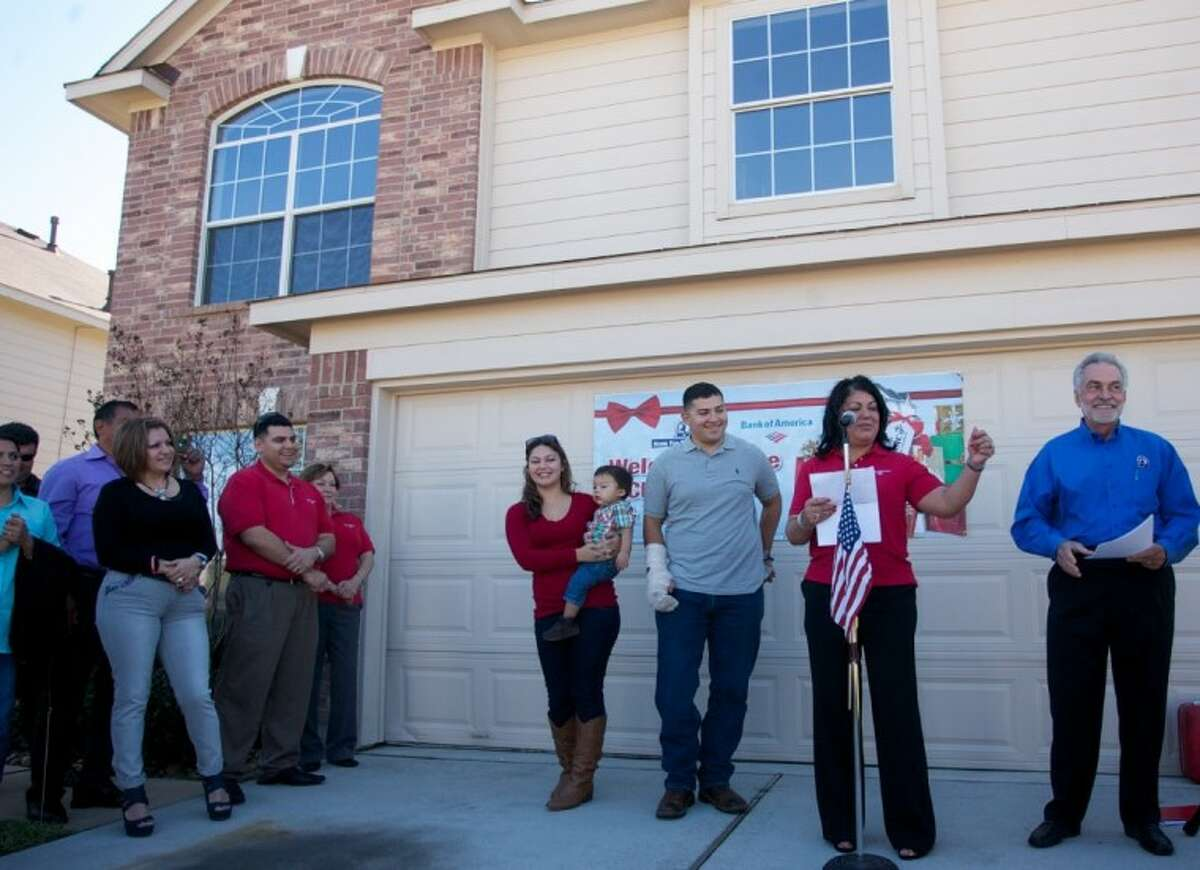 Veteran U.S. Marine Corps Lanc Cpl. Jesse Medina, center and his wife Megan Medina are surprised by the presentation of a new home for the couple in the Bella Noche subdivision of Spring. The home was presented by the Texas Sentinels Foundation and Bank of America.