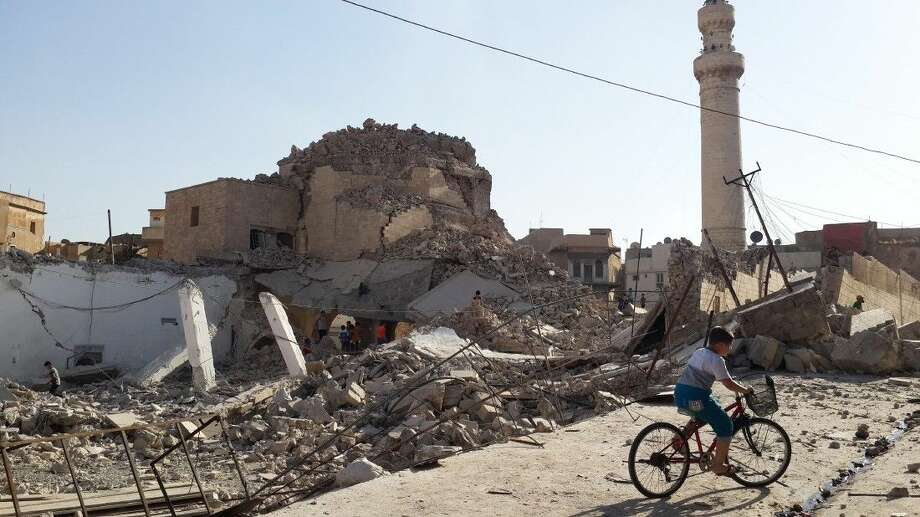 A bicyclist rides by the destroyed Mosque of the Prophet Jirjis on July 27, 2014, in Mosul, Iraq. Photo: Uncredited