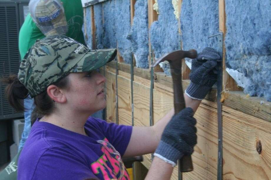 Del Papa Distributing Co. employee Darcie O'Brien installs hurricane straps on a Bay Area - Houston Habitat for Humanity home. Photo: SUBMITTED PHOTO