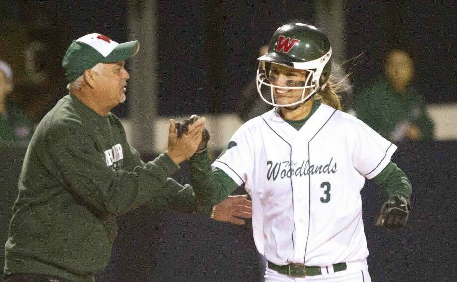 The Woodlands' Abby Langkamp celebrates with coach Richard Jorgensen after her solo home run in the third inning of a softball game against College Park Friday. The Woodlands defeated College Park 10-3. To view or purchase this photo and others like it, visit HCNpics.com.