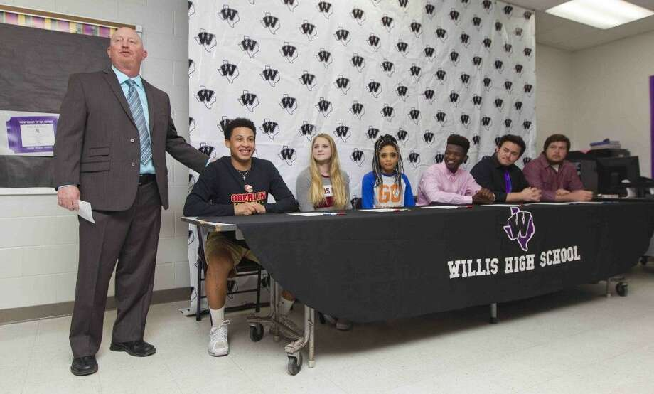 Willis head football coach Audie Jackson jokes with Ceiveon Munoz during a National Signing Day ceremony at Willis High School Wednesday, Feb. 3, 2016. Munoz, who signed to play football for Oberlin Ohio, joined five other Willis athletes who will play various sports at the college level. Photo: Jason Fochtman