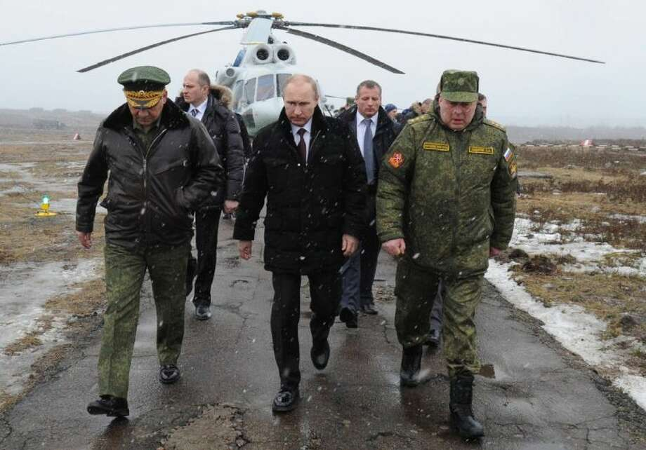 Russian President Vladimir Putin, center, and Defense Minister Sergei Shoigu, left, and the commander of the Western Military District Anatoly Sidorov, right, walk upon arrival to watch military exercise near St.Petersburg, Russia, Monday. Photo: Mikhail Klimentyev