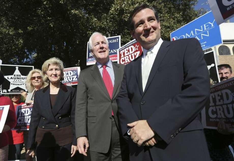 In this Nov. 1, 2012 file photo, then Republican candidate for U.S. Senate Ted Cruz, right, U.S. Senators Kay Bailey Hutchison, left, and John Cornyn listen to a question from reporters outside a polling station in Dallas. Cruz refused to endorse his colleague Cornyn before the 2014 Texas primary. But a resounding Cornyn victory has changed Cruz's mind.
