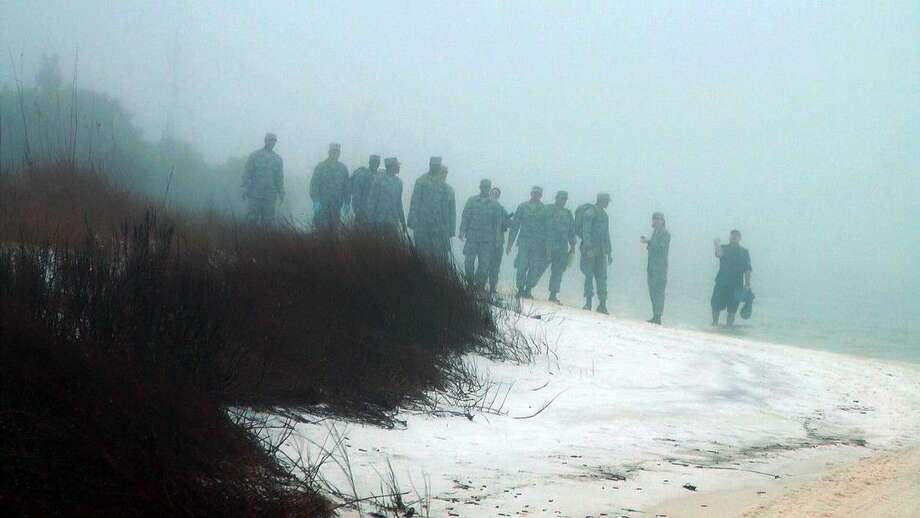 Military personnel on Wednesday search the beach in heavy fog for the wreckage of a military helicopter that crashed late Tuesday with 11 Marines and soldiers aboard at Eglin Air Force Base, Fla. Photo: Melissa Nelson-Gabriel