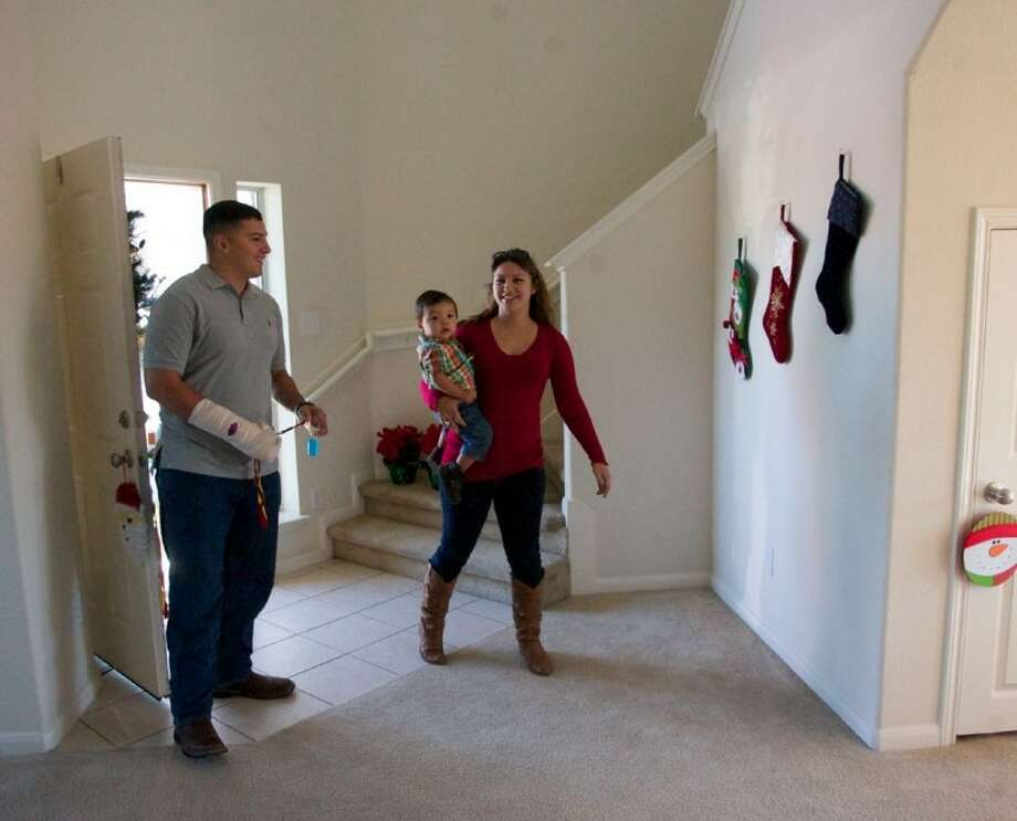 Veteran U.S. Marine Corps Lanc Cpl. Jesse Medina and his wife Megan Medina, walk into their new home for the first time. The couple were surprised by the presentation of a new in the Bella Noche subdivision of Spring. The home was presented by the Texas Sentinels Foundation and Bank of America.