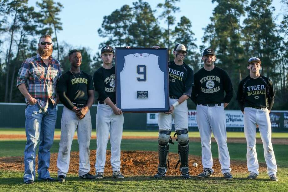 Conroe baseball alum Andrew Cashner stands with seniors from the Conroe baseball team during a ceremony to retire his number on Friday at Conroe High School. Photo: Michael Minasi