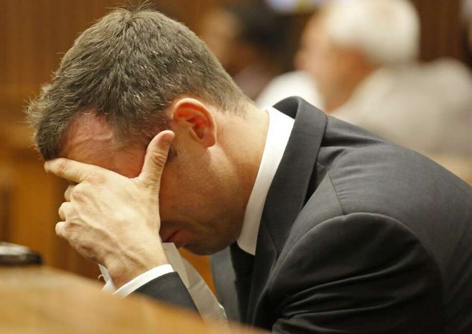 Oscar Pistorius puts his hand to his face as he listens to cross questioning about the events surrounding the shooting death of his girlfriend Reeva Steenkamp, in court during his trial in Pretoria, South Africa, Friday, March 7, 2014. Pistorius is charged with murder for the death Steenkamp, on Valentines Day in 2013. Photo: Schalk Van Zuydam