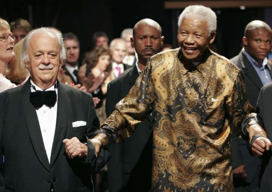In this file photo dated Nov. 12, 2008, George Bizos, left, arrives for his 80th birthday party with former South African president Nelson Mandela in Johannesburg.