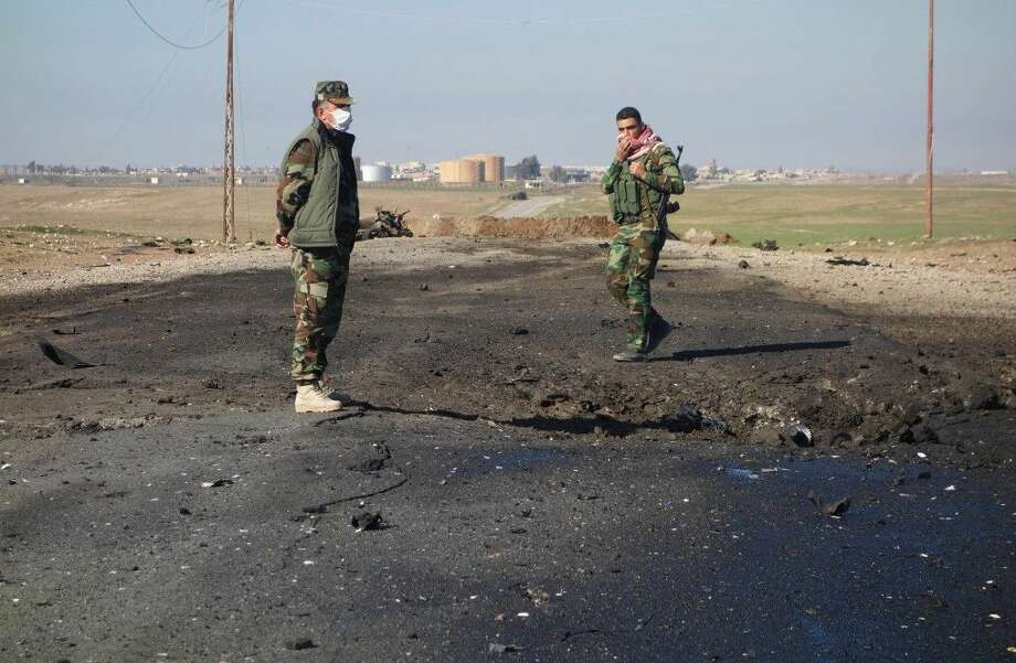 Kurdish soldiers survey the site of a bomb attack on a road between Mosul, Iraq, and the Syrian border. Kurdish authorities in Iraq said Saturday they have evidence that the Islamic State group used chlorine gas as a chemical weapon against peshmerga fighters, the latest alleged atrocity carried out by the extremist organization now under attack in Tikrit.
