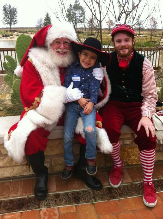"""Gerardo Gutierrez, 6, of Katy, was 'tickled' to meet Santa Claus and Santa's Helper at the """"Stuff the Sleigh of Katy"""" holiday party benefiting pediatric cancer patients at Texas Children's Hospital - West Campus."""