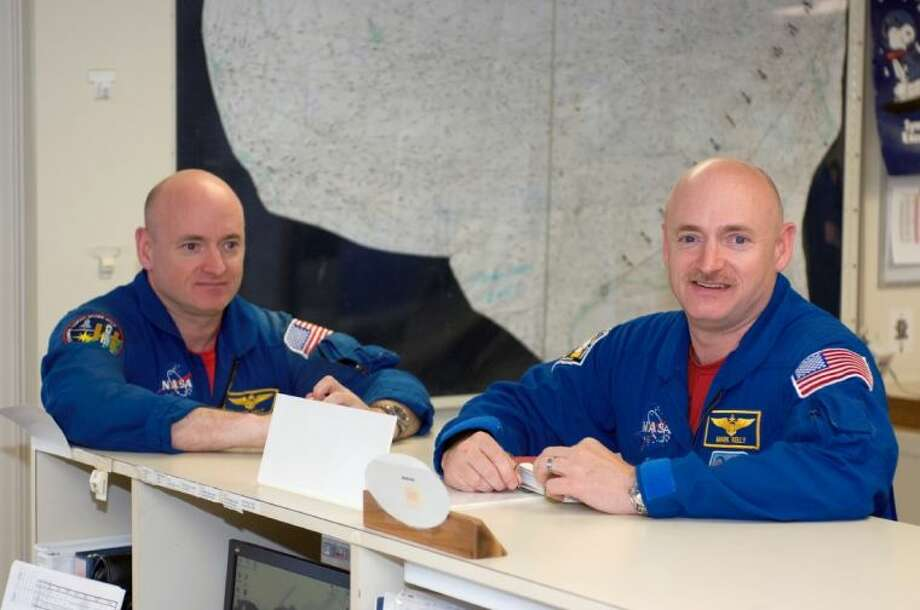 This undated photo provided by NASA, astronauts Mark Kelly, right, STS-124 commander, and Scott Kelly are pictured in the check-out facility at Ellington Field near NASA's Johnson Space Center in Houston. NASA announced Friday that Mark Kelly and astronaut Scott Kelly will participate in 10 different investigations. Craig Kundrot, deputy chief scientist of NASA's Human Research Program, says in a news release that the brothers provide a unique opportunity to study two people with the same genetics who were in different environments. Officials say Scott Kelly spent a year in space while Mark Kelly was on Earth. NASA says it is hoping the studies can be the basis for future research initiatives.