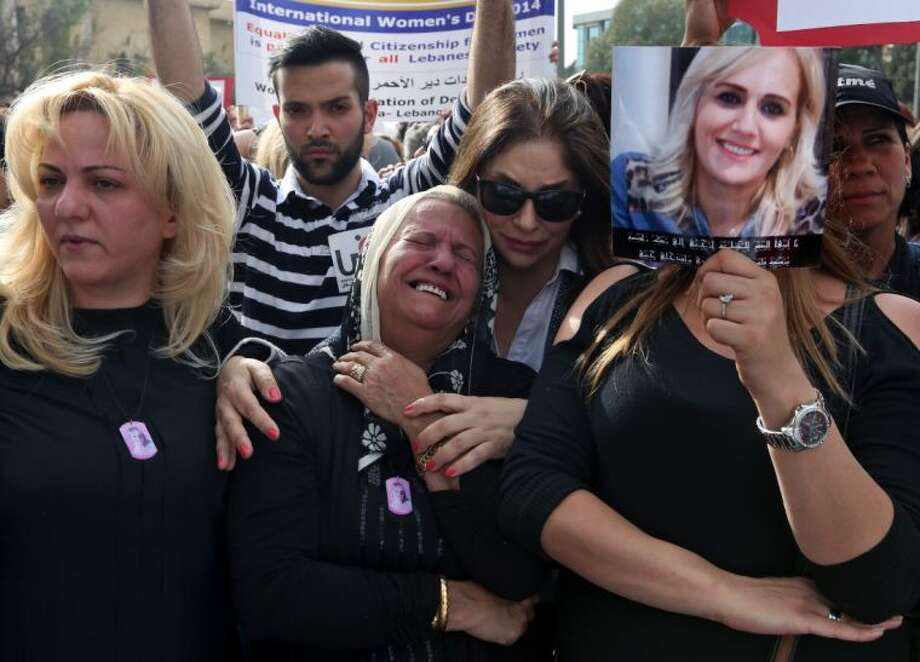 Nada Sabbagh, center, whose daughter was killed by her son-in-law, weeps while taking part in a rally making International Woman's Day demanding that parliament approves a law that protects women from domestic violence in Beirut, Lebanon, Saturday.