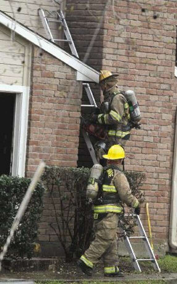 Firefighters work the scene of a fire at Abbey at Conroe Apartments Saturday. Photo: Jason Fochtman