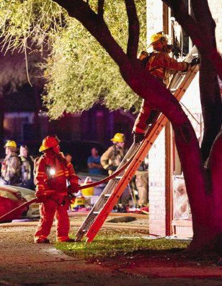 Montgomery County firefighters climb into a second story of a complex at Bellshire Apartments in Conroe on Tuesday evening. A fire destroyed eight units and left three injured. Photo: Jason Fochtman
