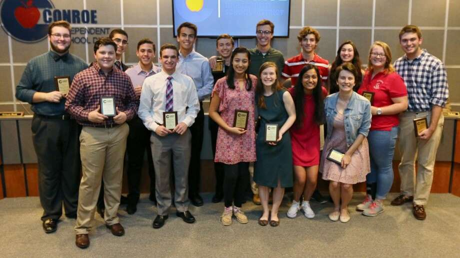 A group of Conroe ISD students stand with their plaques recognizing them as TMEA all-state qualifiers.