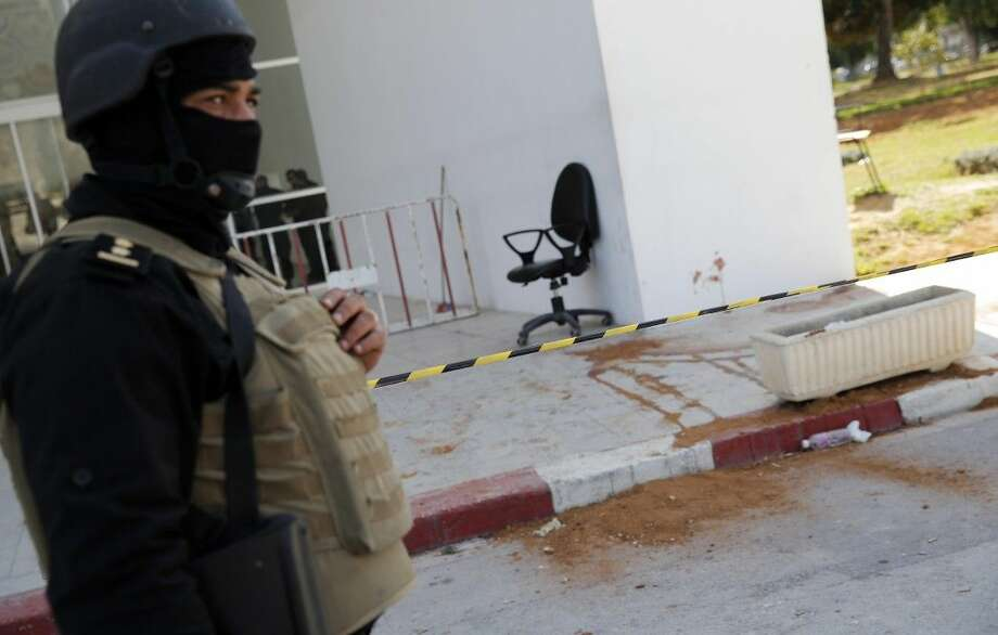 A policeman guard the entrance of the Bardo museum in Tunis, Tunisia, Thursday, March 19, 2015, as a a blood stain is seen at right, a day after gunmen opened fire killing over 20 people, mainly tourists. One of the two gunmen who killed tourists and others at a prominent Tunisian museum was known to intelligence services, Tunisia's prime minister said Thursday. But no formal links to a particular terrorist group have been established in an attack that threatens the country's fledgling democracy and struggling tourism industry.