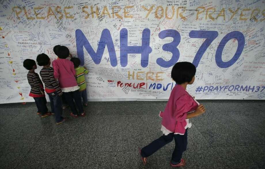 Children read messages and well wishes displayed for all involved with the missing Malaysia Airlines jetliner MH370 on the walls of the Kuala Lumpur International Airport, Thursday, March 13, 2014 in Sepang, Malaysia. Planes sent Thursday to check the spot where Chinese satellite images showed possible debris from the missing Malaysian jetliner found nothing, Malaysia's civil aviation chief said, deflating the latest lead in the six-day hunt. The hunt for the missing Malaysia Airlines flight 370 has been punctuated by false leads since it disappeared with 239 people aboard about an hour after leaving Kuala Lumpur for Beijing early Saturday. Photo: Wong Maye-E