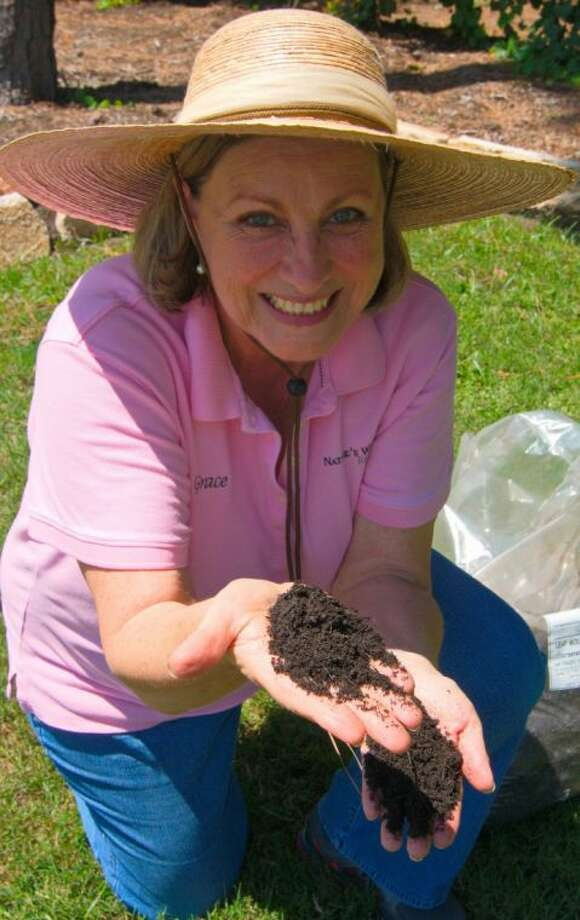 Master Gardener Grace Hernandez shows some soil during a gardening event. Photo: CLIFF ROE