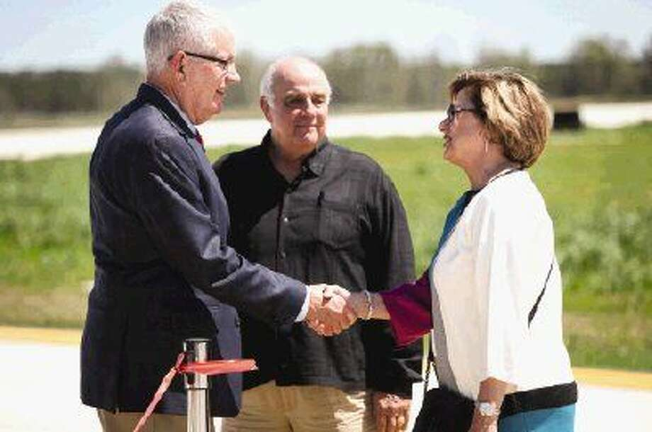 Precinct 1 Commissioner Mike Meador, center, introduces Dave Fulton, director of TxDOT Aviation Division, left, to Judy Campbell, right, during the runway extension ribbon cutting for Lone Star Executive Airport Monday. Campbell donated land needed to complete the runway extension. To view more photos from the ceremony, go to HCNPics.com.