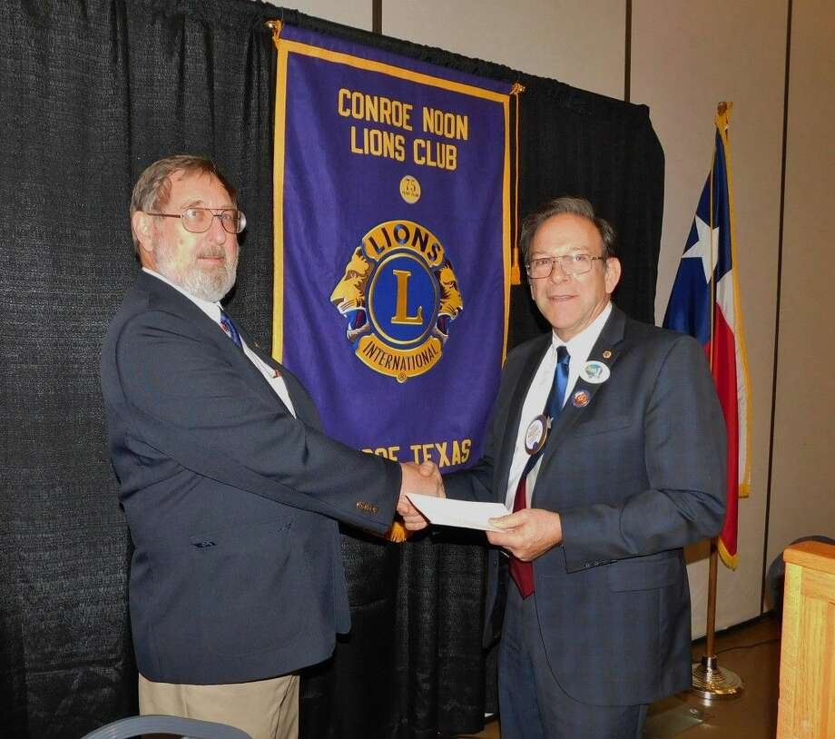 Conroe Noon Lions Club President Karl Johnson, right, presents Lions District Governor Noah Speer, with the Huntsville Lions Club, an honorarium donation to the Texas Lions Camp as part of his annual official club visitation.
