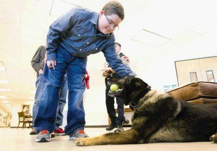 Bryce Everton pets Ranger, a german shepherd service dog with Montgomery County K9-Unit, as he chews on a tennis ball after being honored at the Montgomery County Commissioners Court Meeting Tuesday.