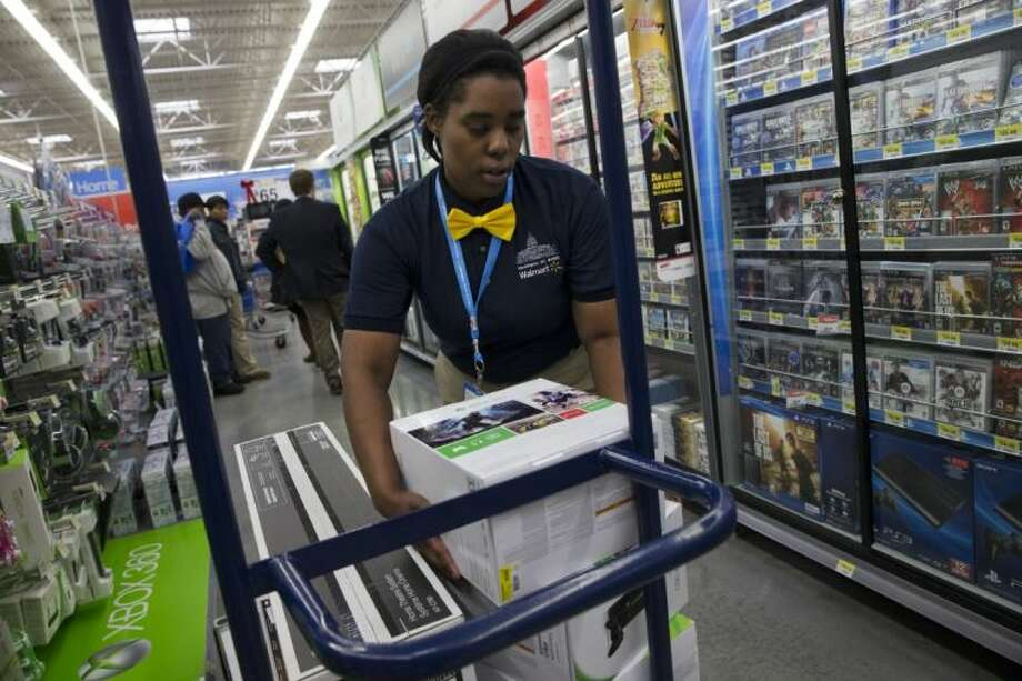 In this Dec. 4, 2013, file photo, Tracey Anderson, 26, re-stocks X-Box sets on opening day of a new Wal-Mart on Georgia Avenue Northwest in Washington. Wal-Mart plans to expand its video game trade-in program to its stores, offering store credit for thousands of video games. Photo: Jacquelyn Martin