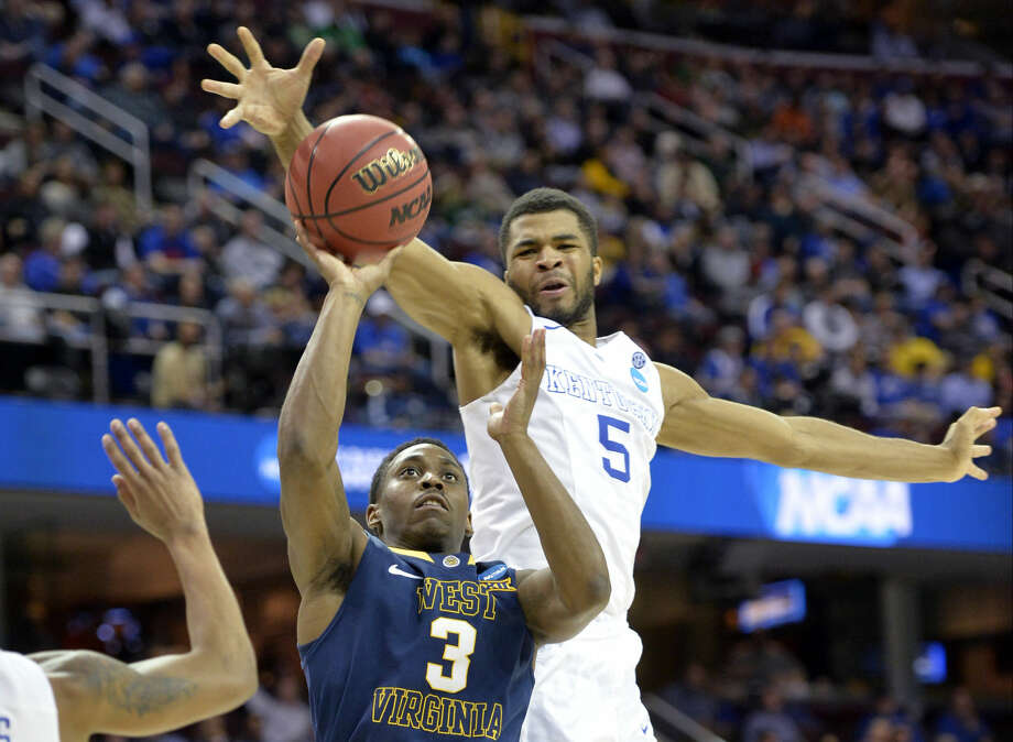 Kentucky's Andrew Harrison (5) swats the ball away from West Virginia's Juwan Staten (3) in the second half of a college basketball game in the NCAA men's tournament regional semifinals, Thursday, March 26, 2015, in Cleveland. (AP Photo/David Richard) Photo: David Richard