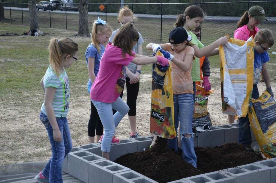 Fifth-grade students at Grangerland Intermediate School work to build a school garden as a part of the Learn, Eat, Grow & Go! program on Feb. 19.
