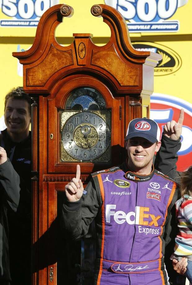 Denny Hamlin poses next to the winner's trophy after the NASCAR Sprint Cup Series auto race at Martinsville Speedway. Photo: Steve Helber