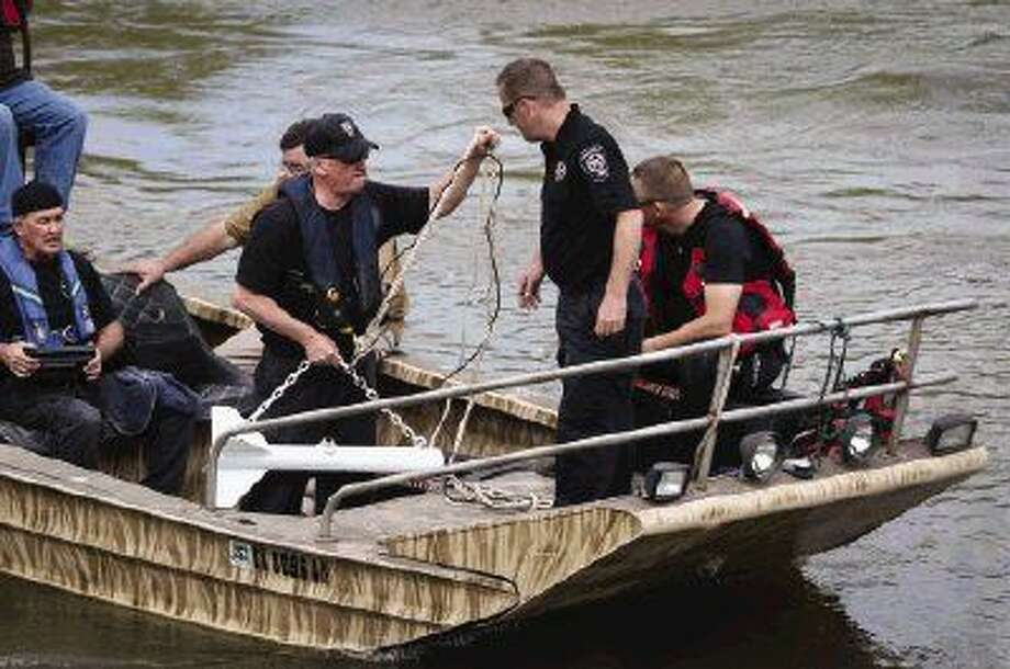 Members of the Montgomery County dive team search the west fork of the San Jacinto River for the body of Librado Rubio Monday. According to witnesses, Rubio was thrown from a horse Sunday afternoon while trying to cross the river. Photo: Michael Minasi