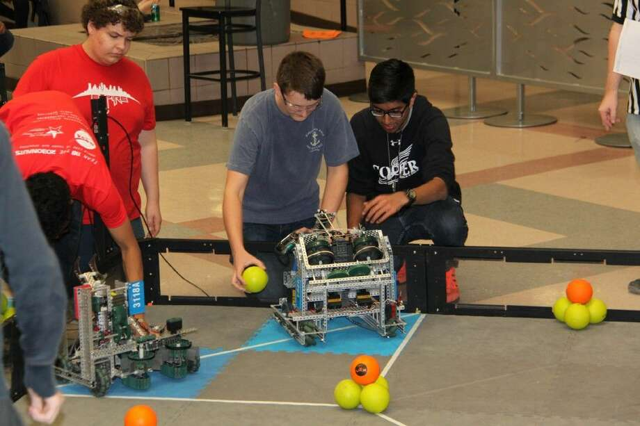 "Cooper robotics team members, junior Yusuf Baig and senior Francisco Masuelli, work on ""Cooper One"" at the VEX ""Battle by the Beach"" competition in Galveston."