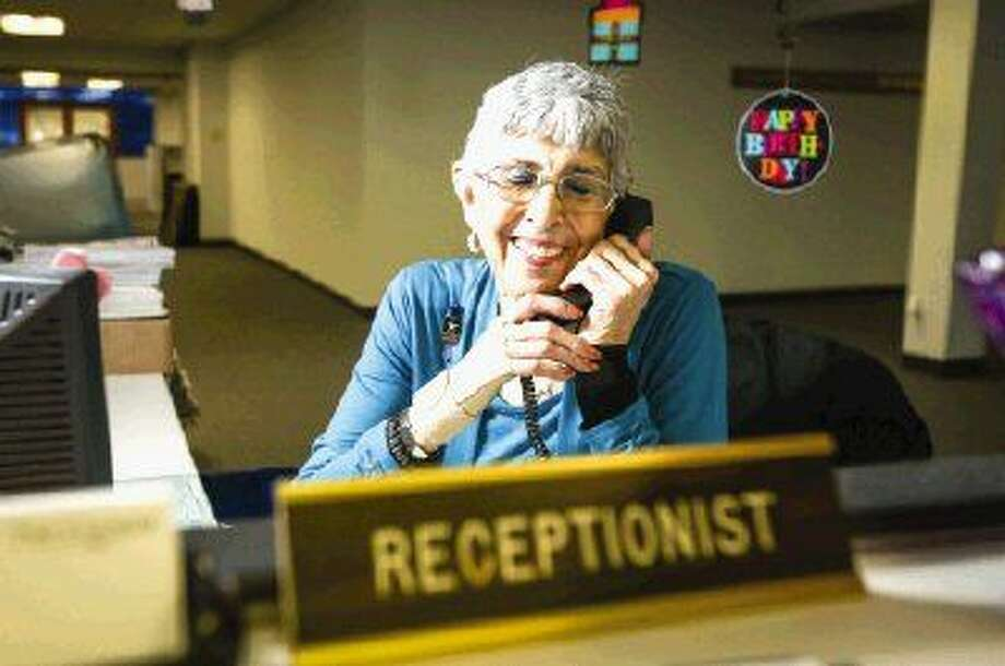 Receptionist Rita Crosby receives a happy birthday wish from a friend during a phone call Monday at The Courier. Crosby turned 80 Monday and has been working at the local newspaper for 23 years. Photo: Michael Minasi