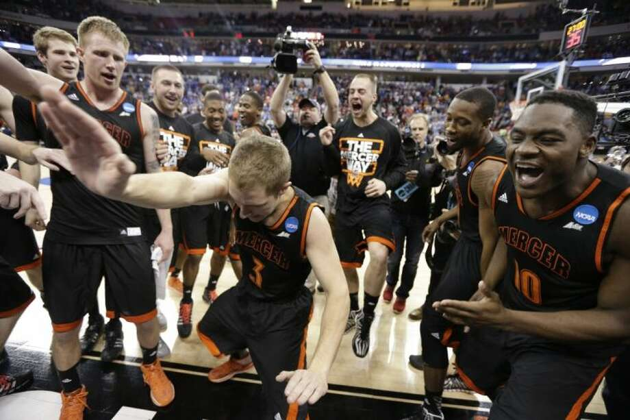 Mercer guard Kevin Caveneri leads an impromptu dance after the Bears upset third-seeded Duke 78-71. The Woodlands Christian Academy graduate James Bento, a Mercer freshman, is pictured third from right. Photo: Chuck Burton