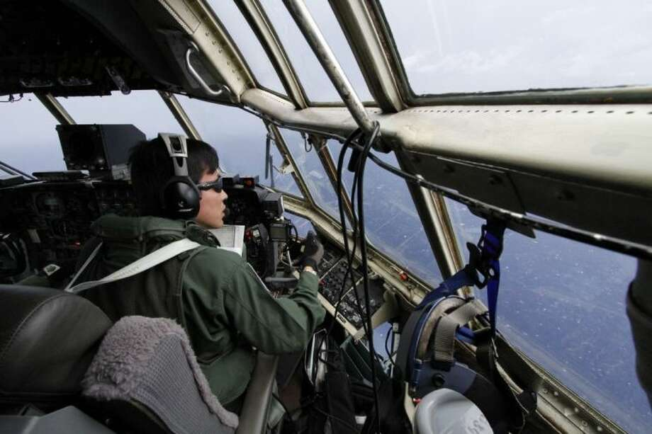 Japanese Air Self-Defense Force copilot Ryutaro Hamahira scans the ocean aboard a C130 aircraft while it flies over the southern search area in the southeastern Indian Ocean, 124 to 186 miles south of Sumatra, Indonesia, Friday.